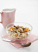 Muesli with nuts and dried fruit, small jug of milk