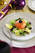 Crab salad wrapped in smoked salmon with caviar and salad leaves
