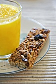 Granola bar with a glass of orange juice