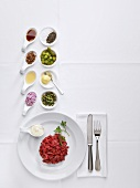 Ingredients for steak tartare on white tablecloth