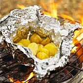 Potatoes in aluminium foil on a barbecue