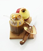 Apple caramel sauce in a jar and a peeled apple on a chopping board