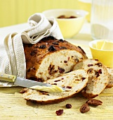 White bread with cranberries and caramelised pecans, partly sliced