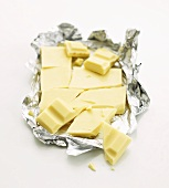 Broken white chocolate in silver paper