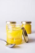 Three jars of honey, one opened