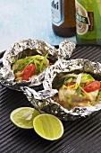 Fish fillets in aluminium foil on grill