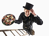 Chimney sweep on ladder holding plate of muffins