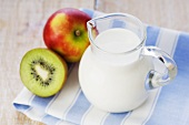 Milk in glass jug, apple and kiwi fruit