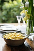 Ribbon pasta with butter on wooden table with spring flowers