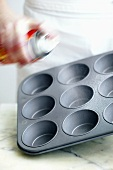 Spraying muffin tin with oil