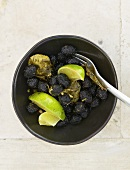 Dried black olives with lime wedges and coriander