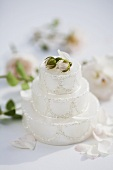 White candle in shape of cake, rose buds