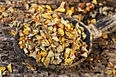 Dried turmeric root on wooden spoon