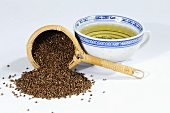 Perilla seeds with tea strainer and cup of tea