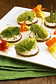 Canapés with bean puree and nasturtium flowers