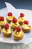 Passion fruit cream and raspberries in pastry shells