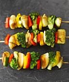 Three vegetable skewers on slate background