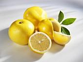 Mehrere gelbe Grapefruits (ganz, halbiert und Schnitz)