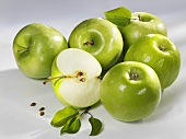 Several green apples (whole and halved)