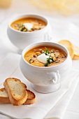 Pumpkin and orange soup with pumpkin seeds and sour cream