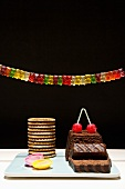 Still life with chocolate cake, biscuits and Gummi bears