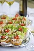 Canapes with ham, cheese and tomato on silver platter