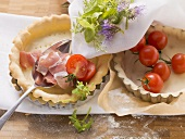 Ingredients for tarts: pastry cases, bacon, tomatoes, herbs