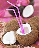 Aufgeschlagene Kokosnuss mit Strohhalmen