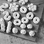 Meringue in various shapes drying on marble slab