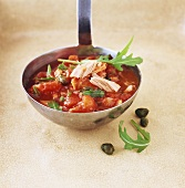 Tomato sauce with tuna, rocket and capers on ladle