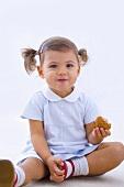 Kleines Mädchen hält angebissenes Muffin