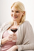 Blond woman holding glass of red wine