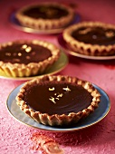 Small chocolate tarts with gold leaf on gold-rimmed saucers