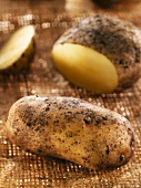 Potatoes, whole and partly sliced, on hessian