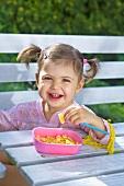 Little girl eating pasta in garden