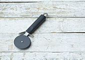 Pizza cutter on wooden background