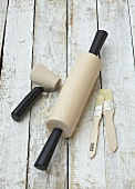 Rolling pin, small pastry roller and pastry brushes on wooden background