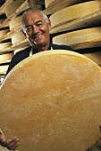 A man holding a large wheel of cheese (Comte)