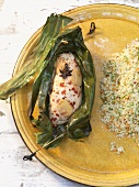 Marinated corn-fed poularde in banana leaf on couscous salad