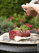 Seasoning beef fillet on barbecue with pepper