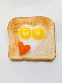 Fried eggs in heart-shaped hole in slice of toast