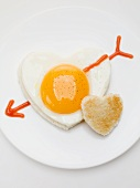 Heart-shaped fried egg with ketchup arrow and heart-shaped toast