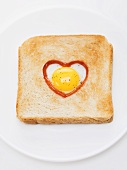 Heart-shaped fried egg with ketchup in slice of toast
