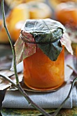 Persimmon and pumpkin chutney with ginger in jar