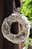 A door wreath of dandelion clocks, guinea fowl feathers and felt yarn