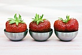 Three strawberries in small metal dishes