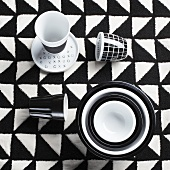 Black and white cups and bowls on checked tablecloth