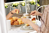 Two women eating a Hefezopf (sweet bread from southern Germany) for breakfast on the terrace