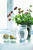 A jug of water, lemons and flowers on a table