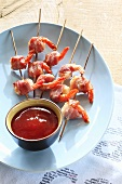 Barbecued bacon-wrapped prawns on wooden skewers, ketchup